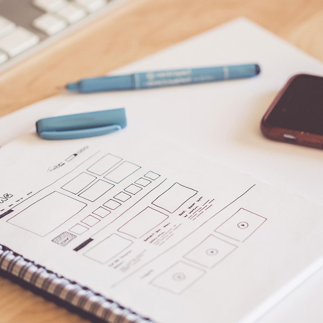 Designer sketching out wireframes for website