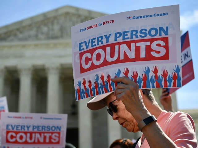 "Image of a man holding a sign that says ""Every person counts"" outside of the U.S. Supreme Court."