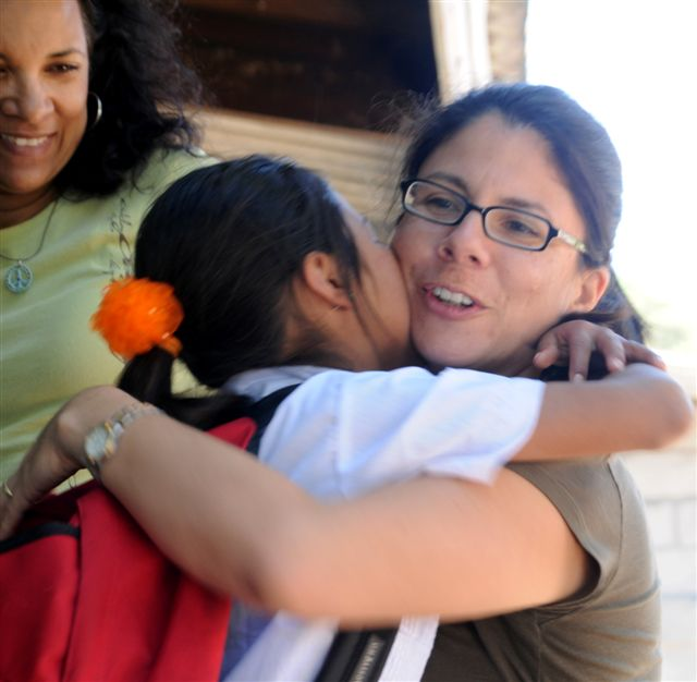 teacher hugging young student on Back to School Day