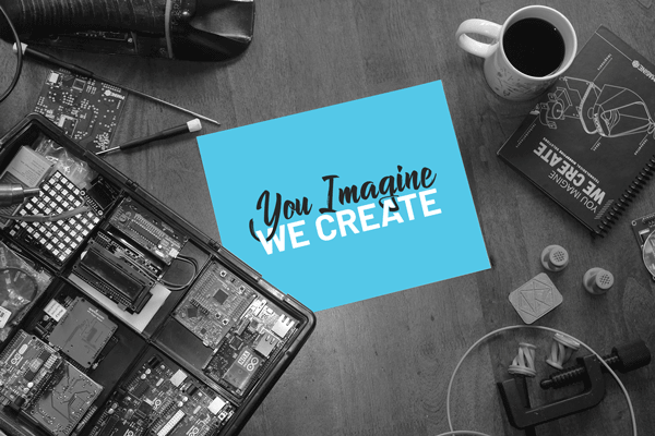 image of a desktop with electronics and design tools, and coffee, and a paper with a the legend You Imagine We Create