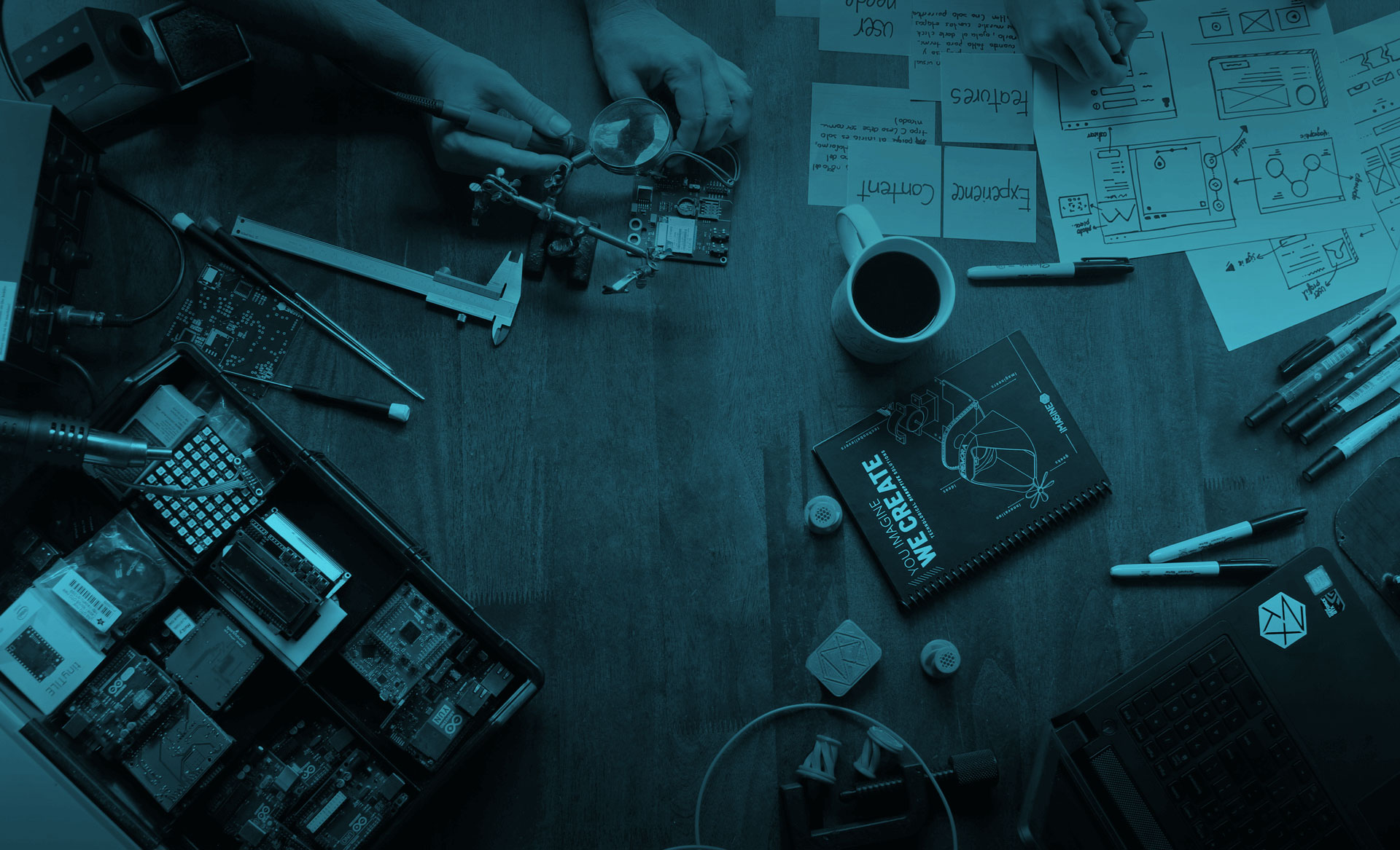 image of a desktop with electronics and design tools, and coffee