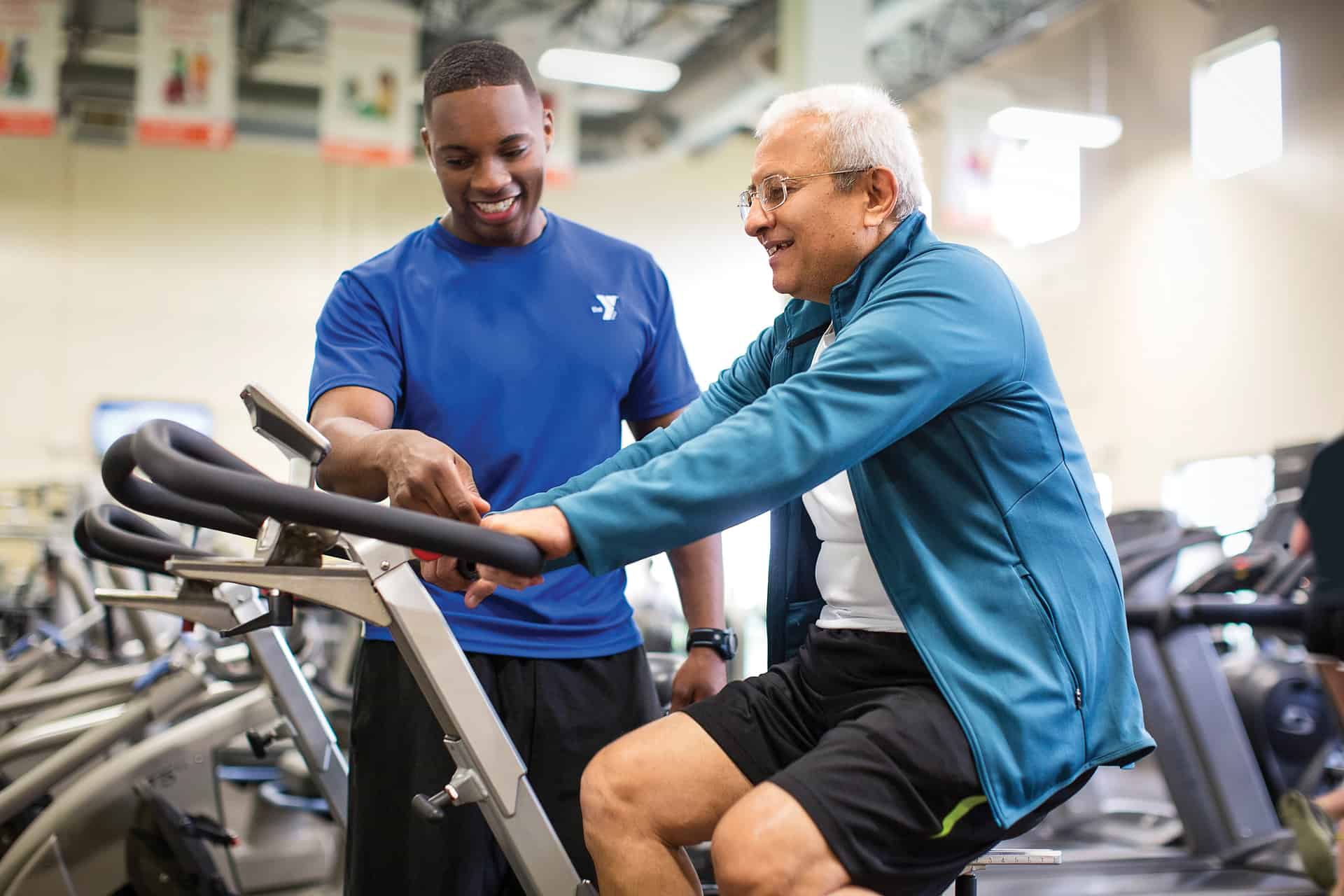 Male personal trainer showing senior how to use stationary bike functions.