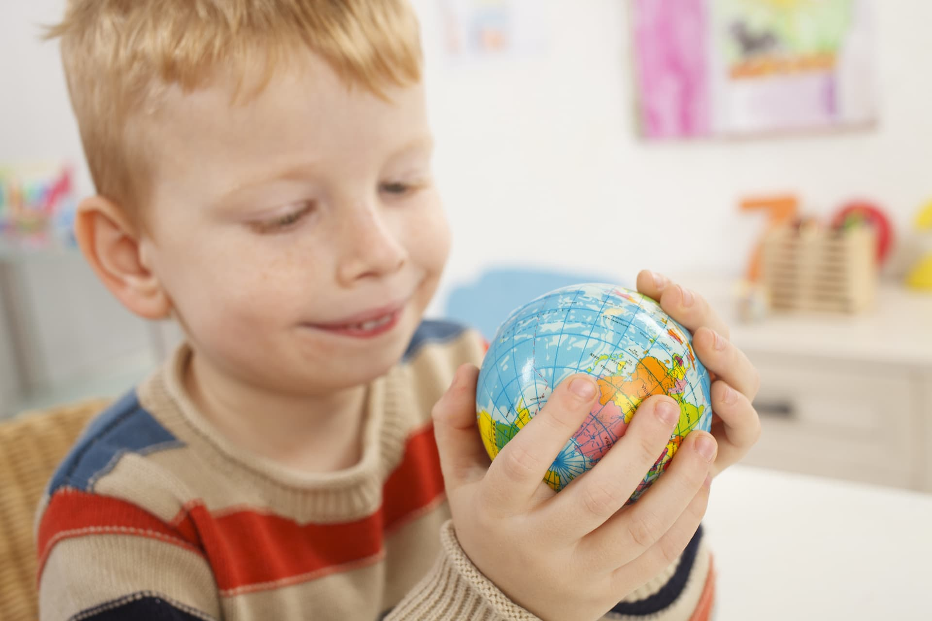 A young boy holding and smiling at a small globe of the world