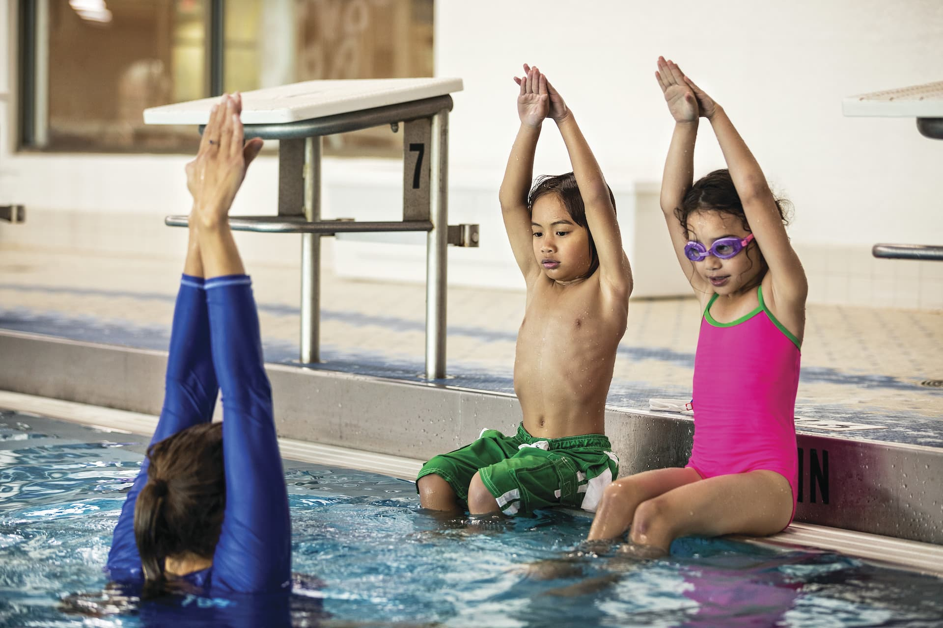 Children practicing diving technique on pool edge while instructor shows them the proper technique.