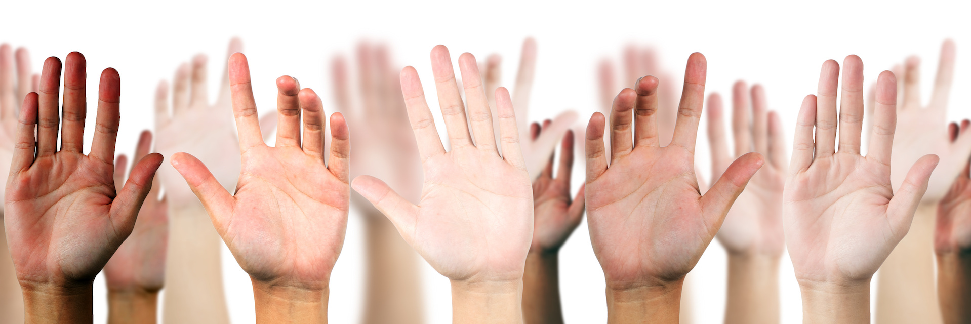 A group with their hands raised offering to volunteer