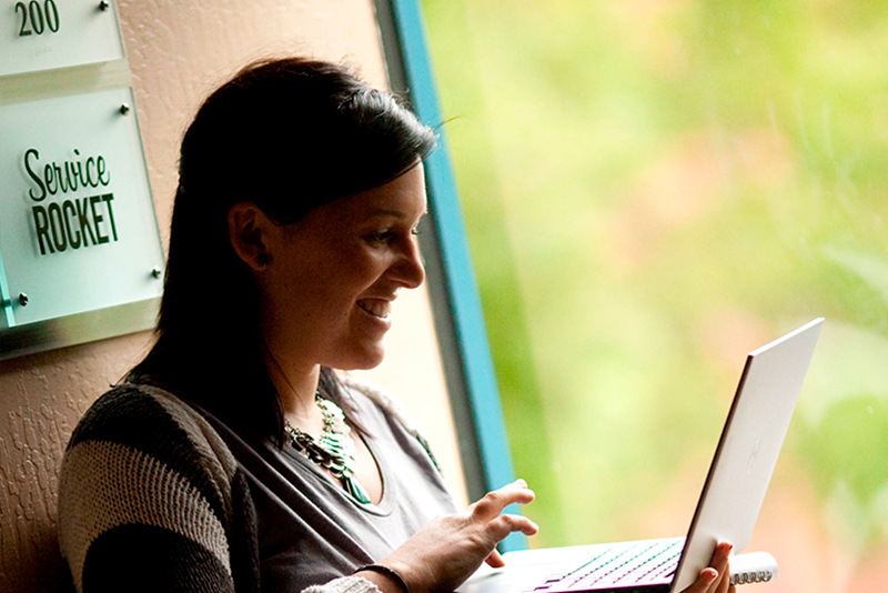 A smiling female ServiceRocket customer. leaning against a wall, tiping on her laptop, next to a window.