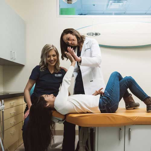 Photo of a Dr. Sarah Wildey with a team member standing next to a patient on the treatment table