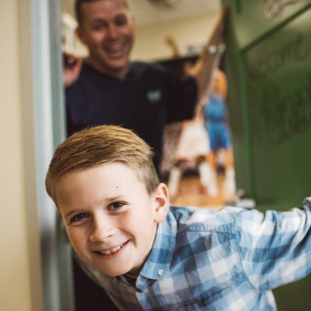 Photo of a boy smiling with Dr. Wildey standing in the background