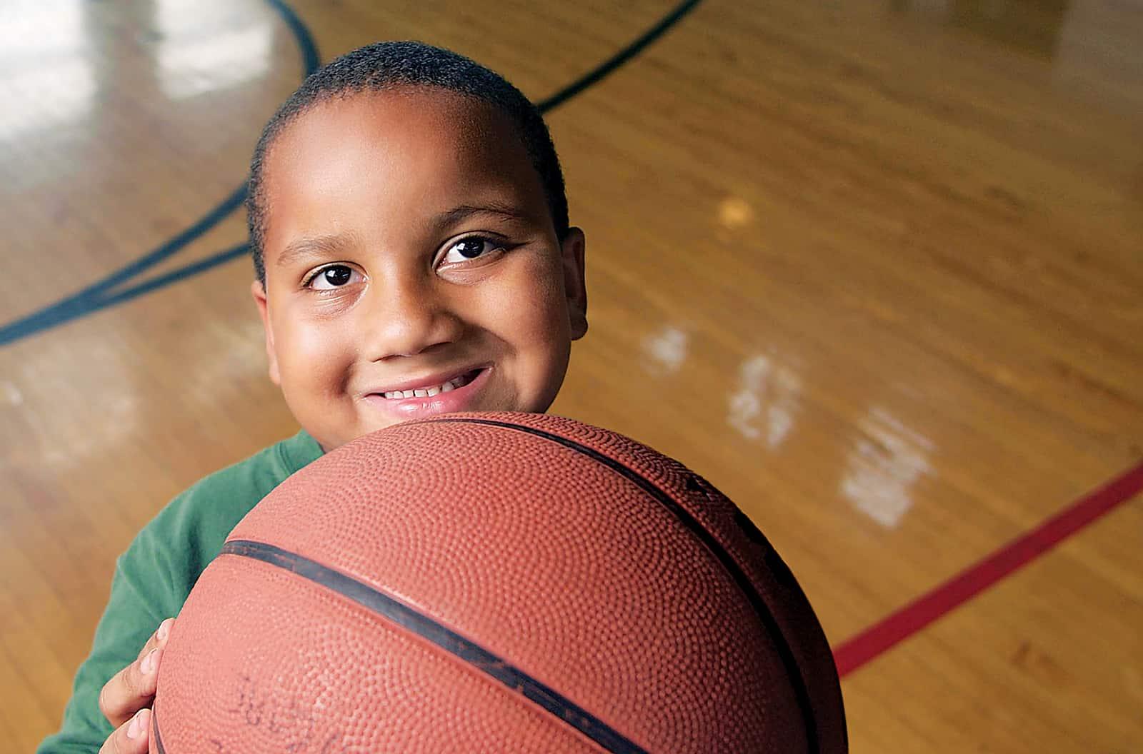 Boy holding basketball on court