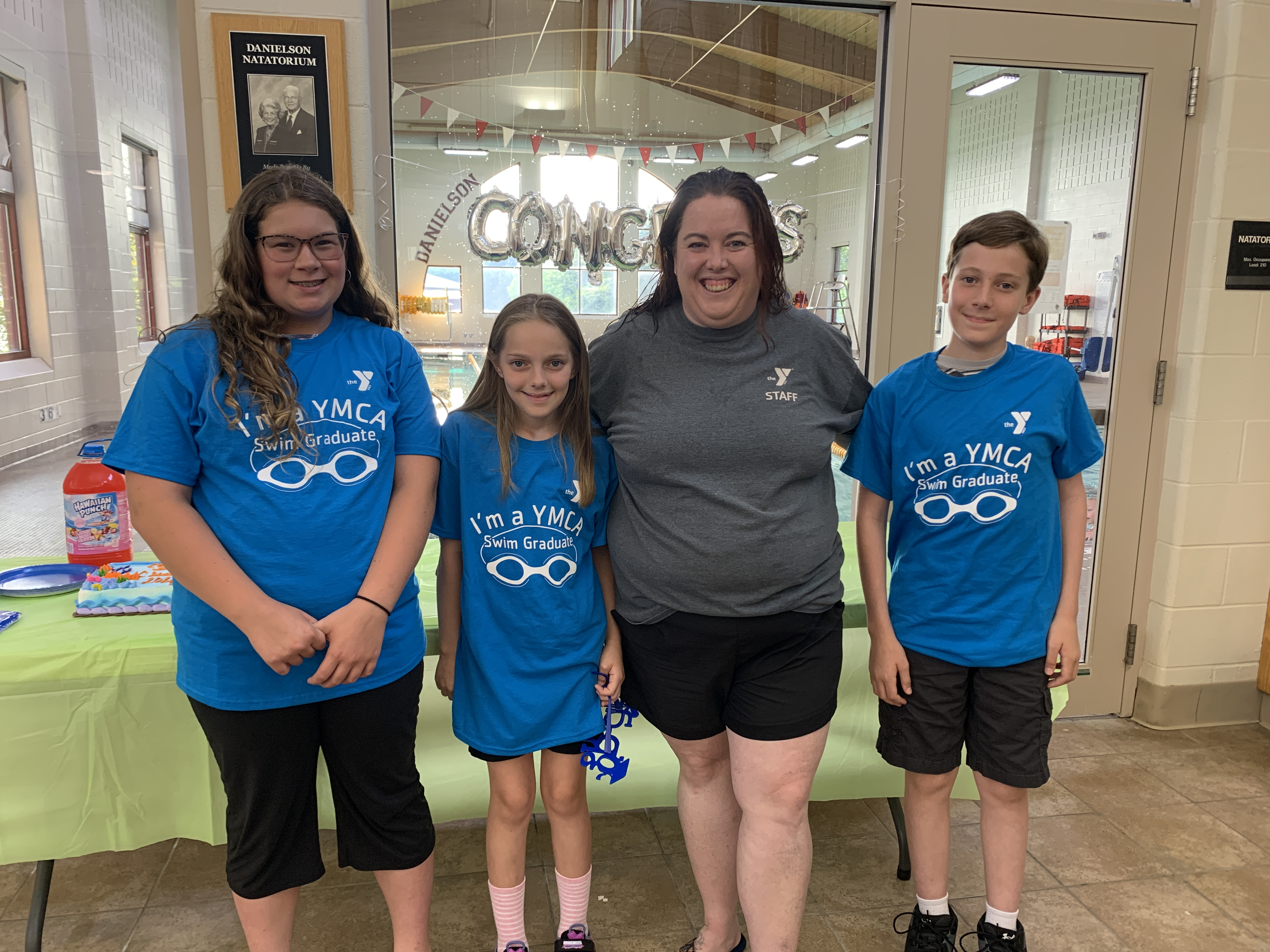 Maggie Williamson, Peter Mackie, and Saida Mackie each completed the lessons and evaluations needed to receive acknowledgment of their swimming accomplishments. Pictured with Natasha Hamilton.