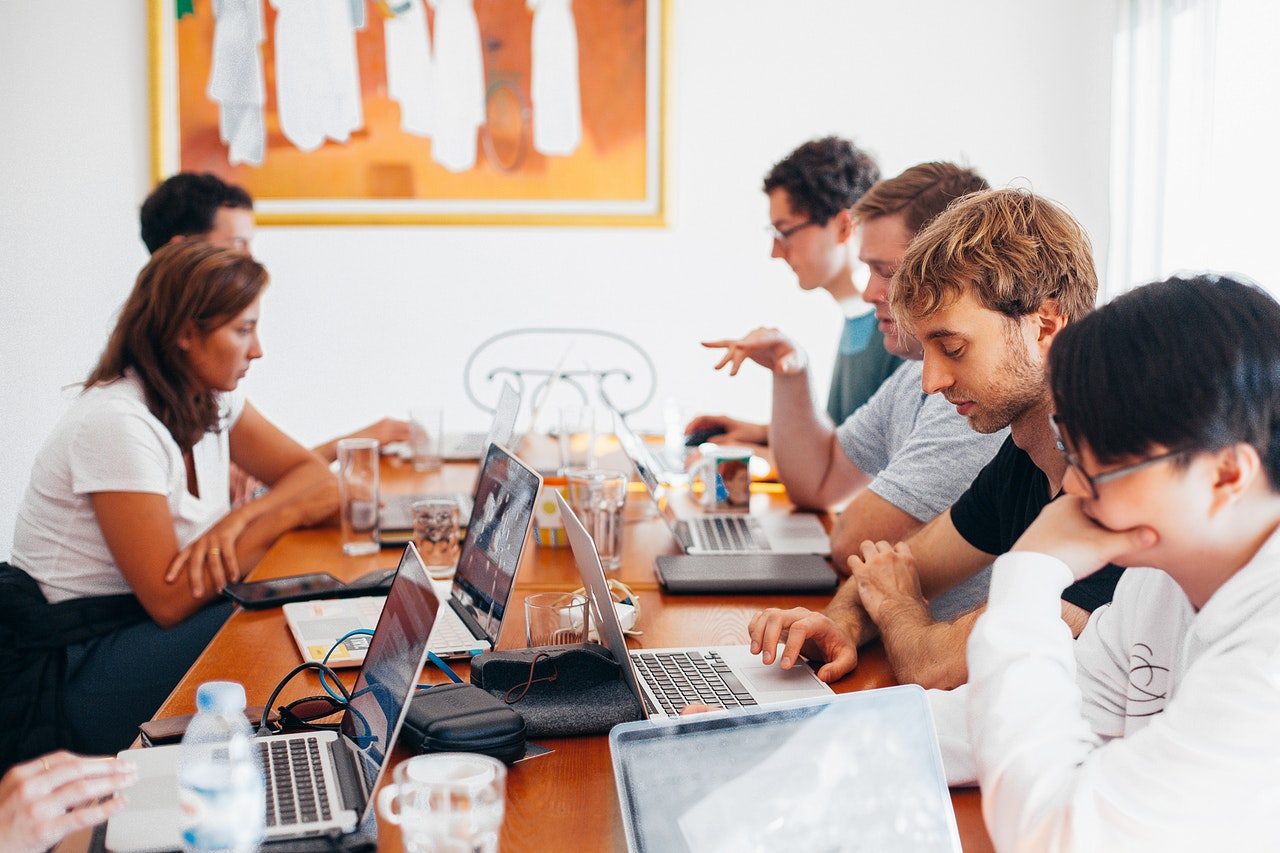 SMART Goals Template: People gathered around a table with laptops