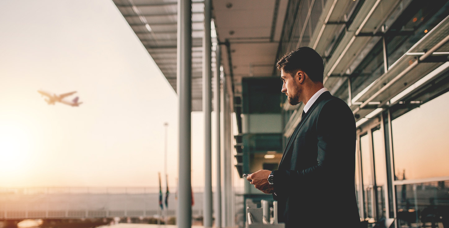 Business travel insurance business man at airport with plane in background looking at watch