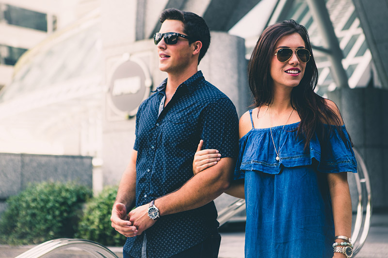 Couple holding arms in blue clothing with sunglasses on leaving a building