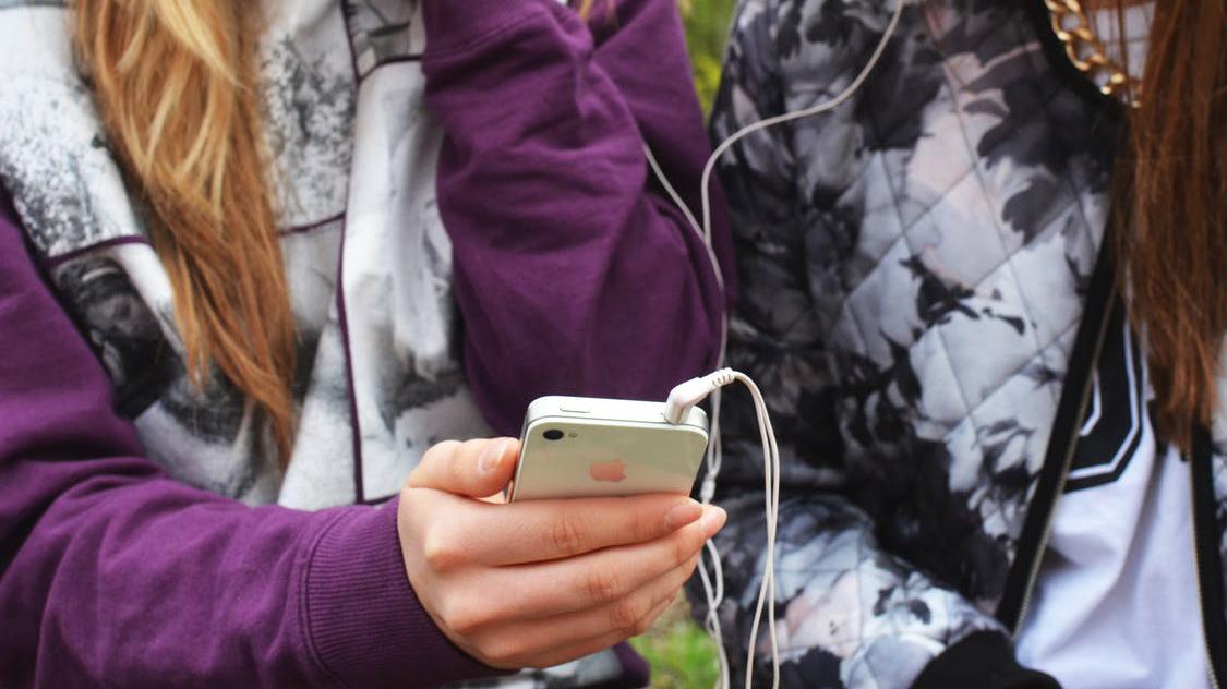 To jenter som bruker mobiltelefon.