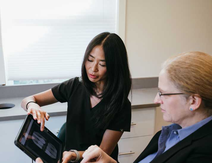 Photo of Dr. Cheung and patient looking at x-rays on an iPad