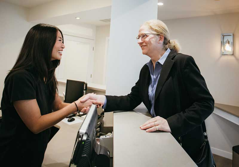 Photo of Dr. Cheung greeting a female patient at the reception desk