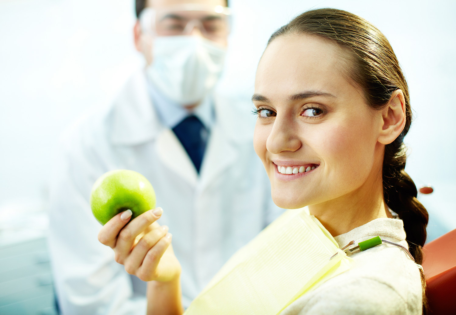 Young woman smiling at dentist green apple