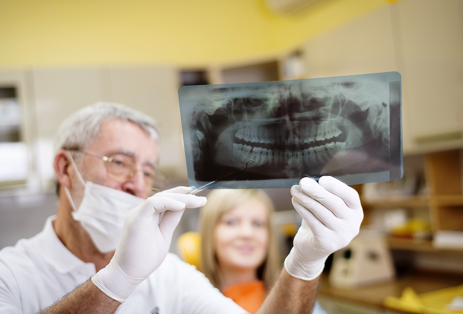 Dentist showing x-ray of teeth to patient