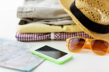 Clothes, hats, sunglasses, phone and a map