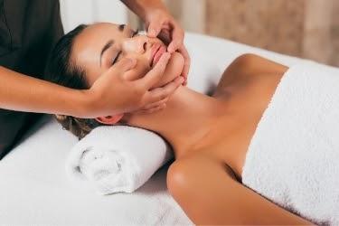 Woman in a spa receiving a facial massage