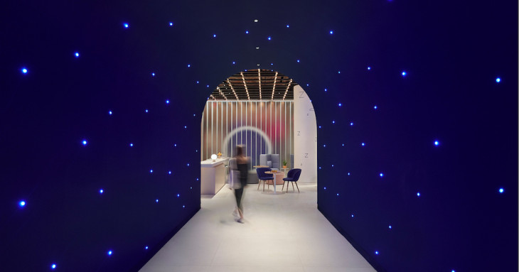 Futuristic blue corridor with lights and person exiting at the end