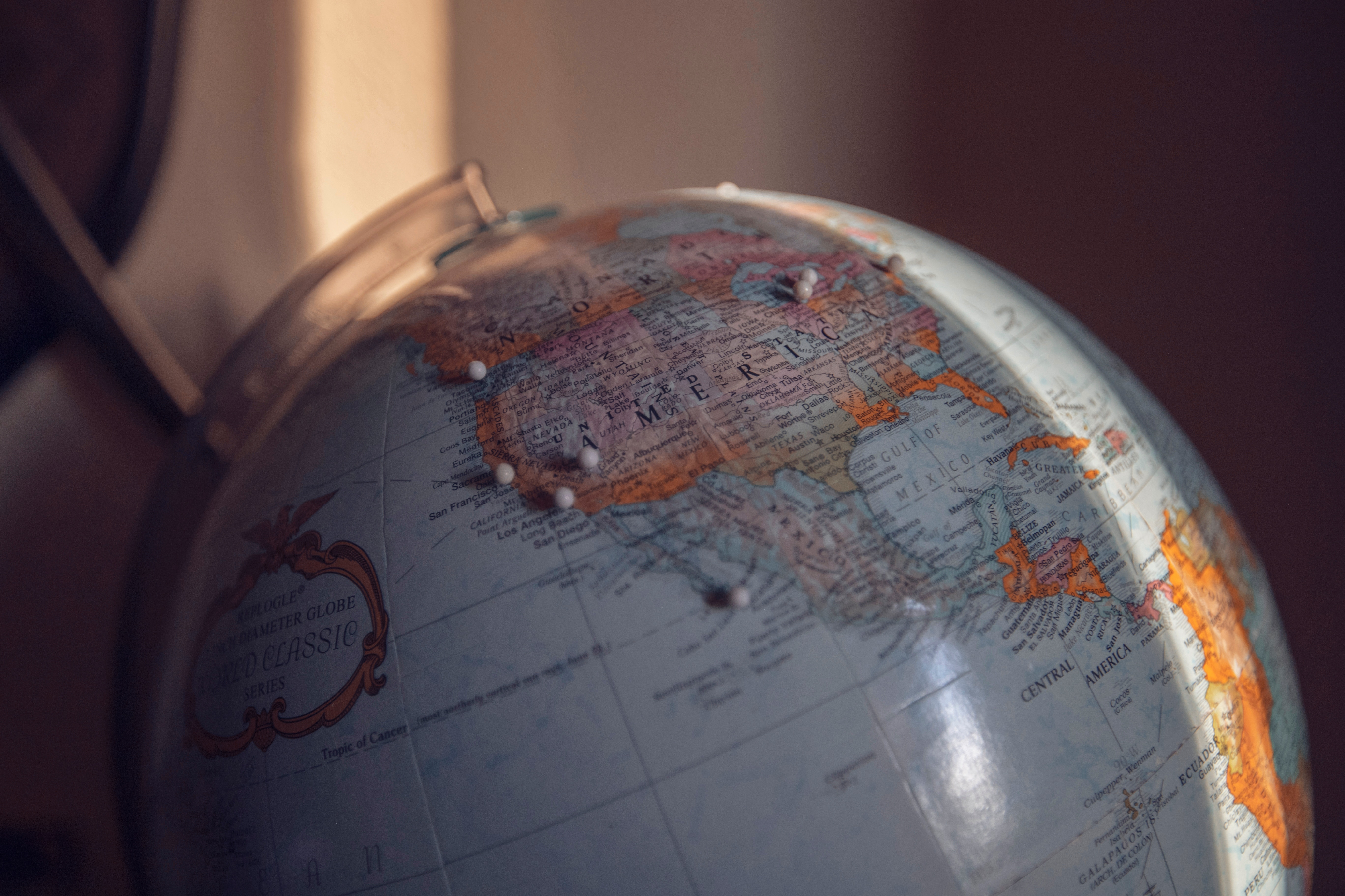 A globe with pins stuck in different locations