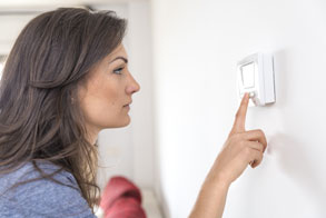 Woman checking thermostat