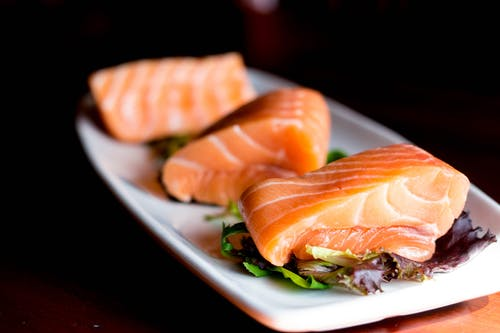 Three cuts of salmon sitting on a long white plate, each on top of a piece of lettuce
