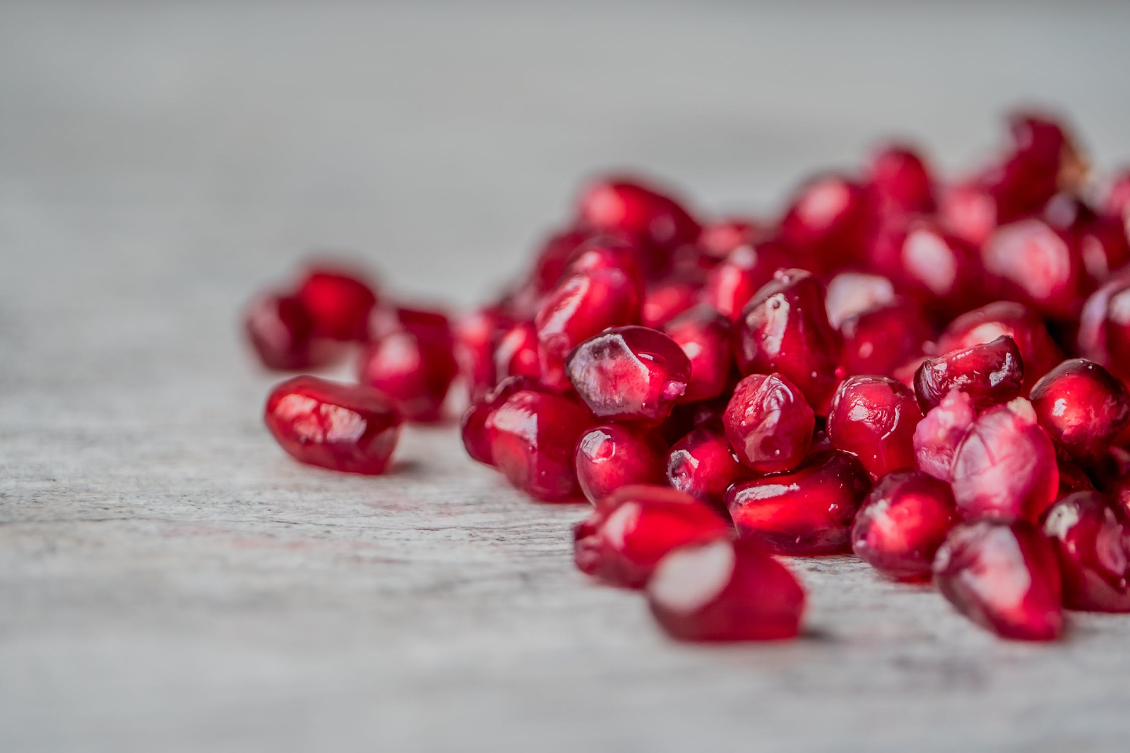 Pomegranate seeds scattered on a gray background