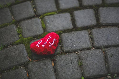 a heart shaped pillow that reads you are not alone on a stone patio