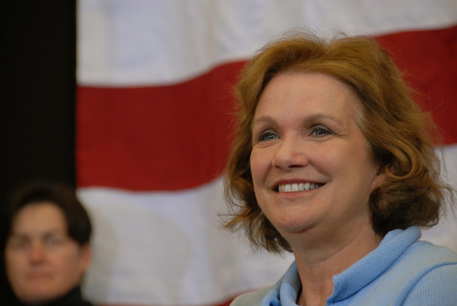 Elizabeth Edwards posing in from of American Flag