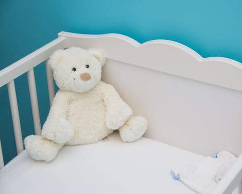 a white teddy bear in a crib