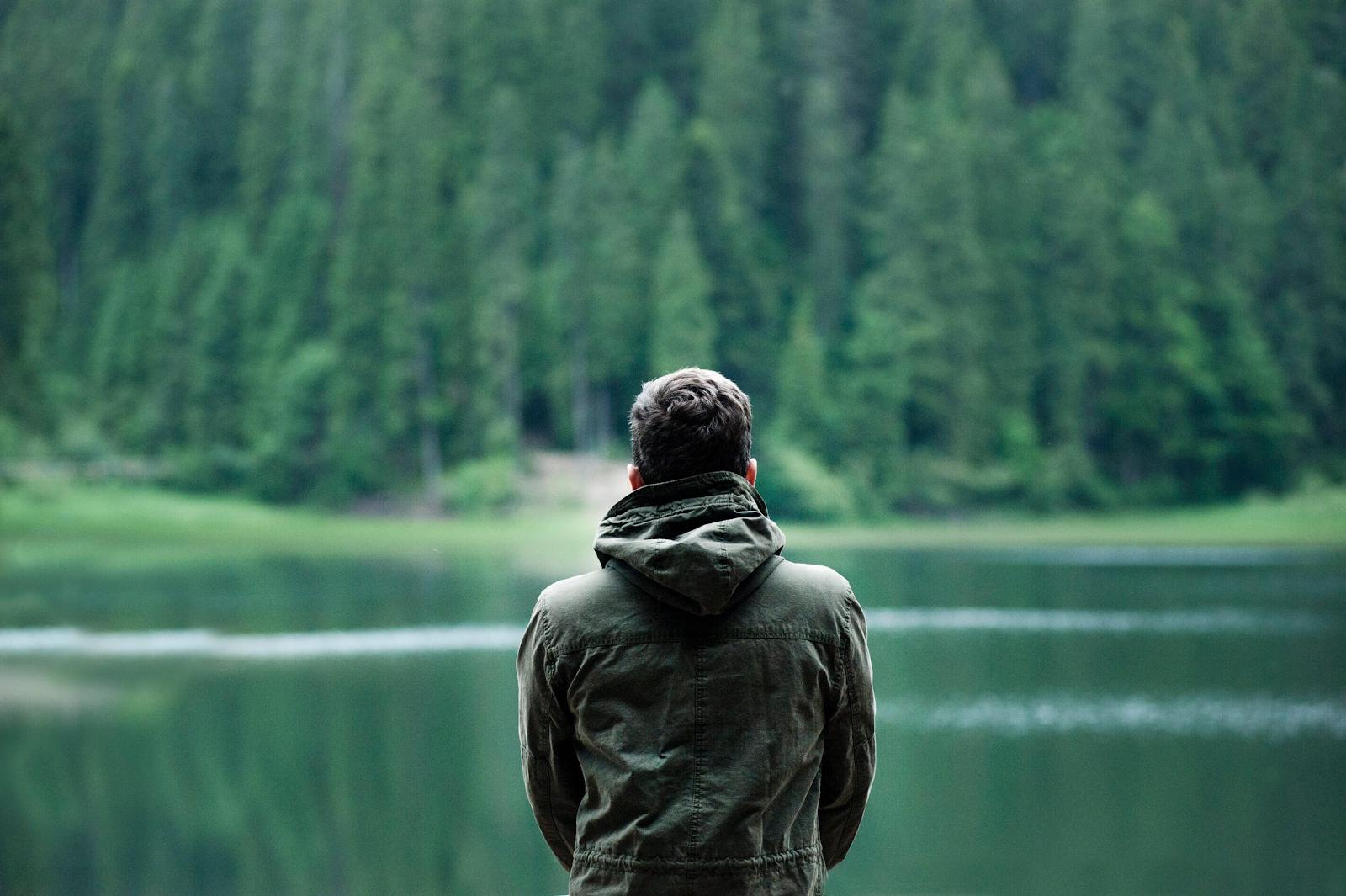 man looking at a lake