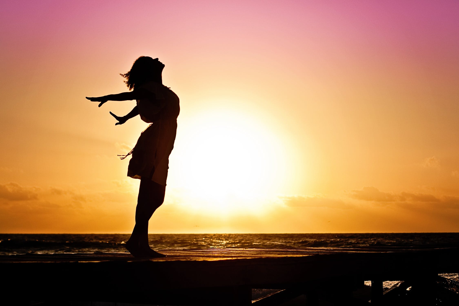 woman stretching with the sunrise