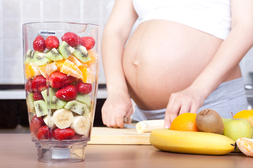 Pregnant woman cutting fruit for blender