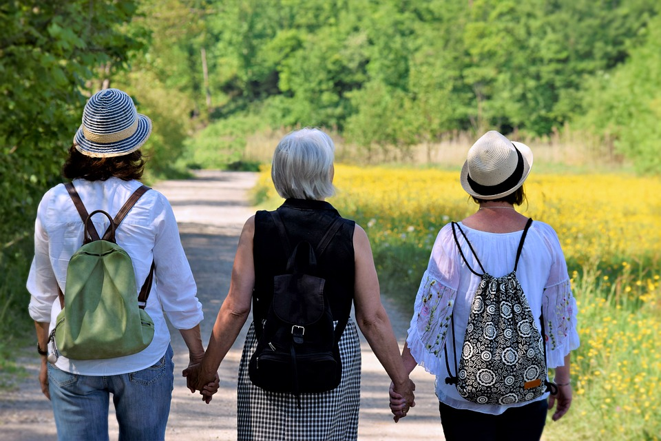 A mother, daughter, and granddaughter hold hands in the park on  sunny day.