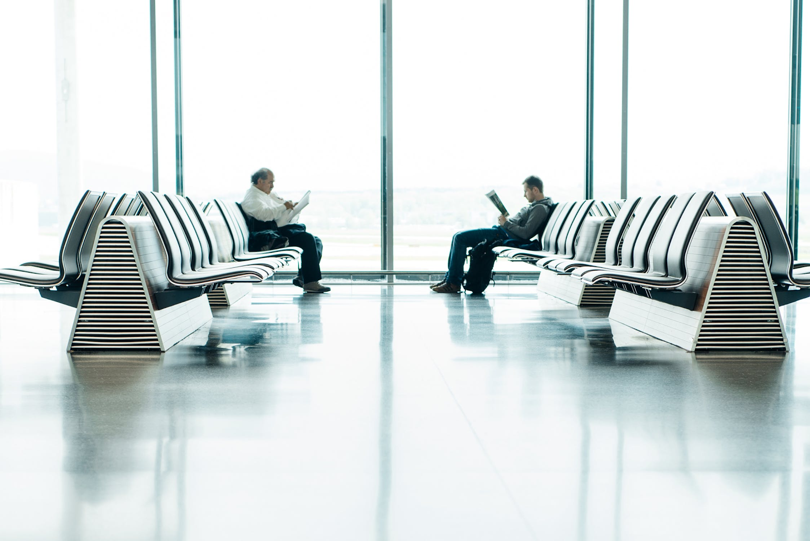 men sitting at an airport gate