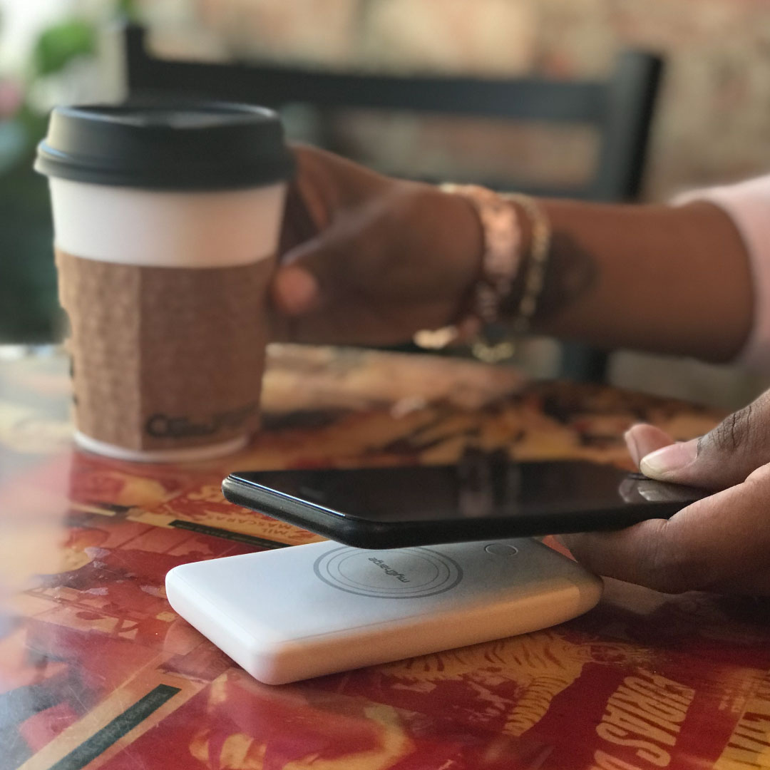 person using UnPlugged Wireless Portable Charger while holding a coffee cup