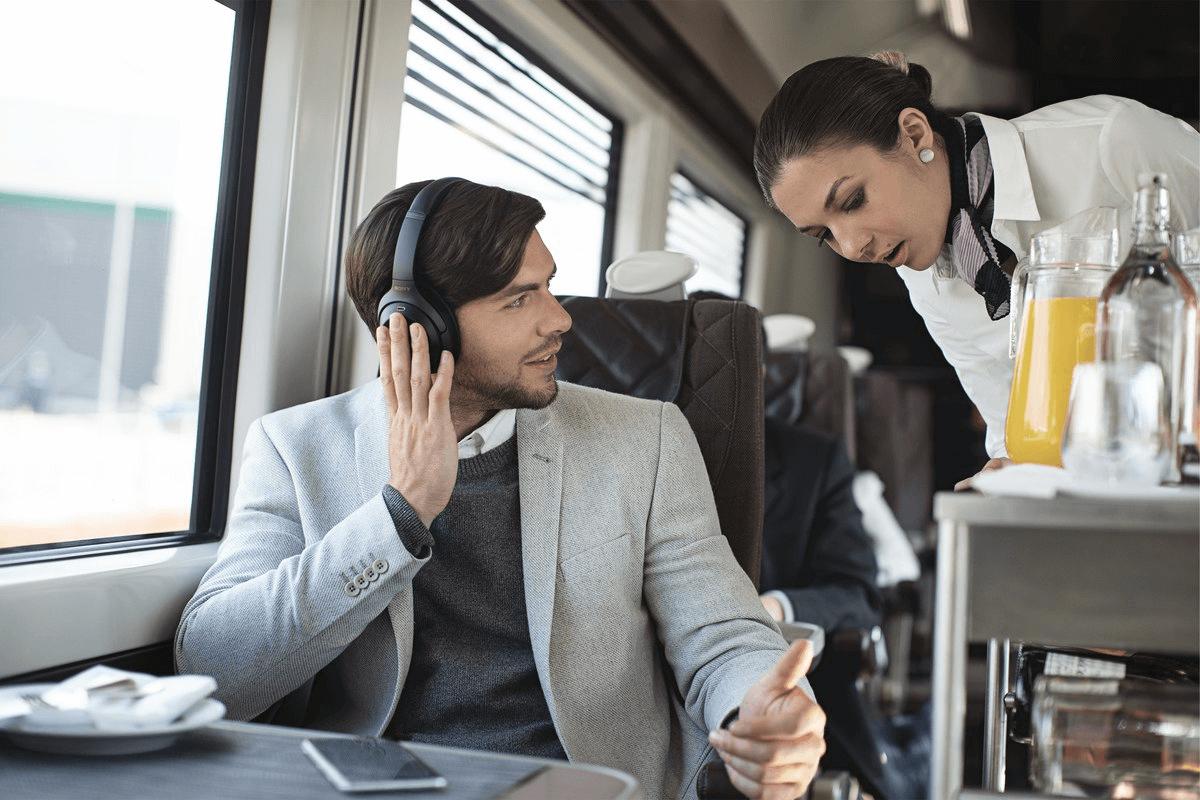 Man on train talking to stewardish wearing Sony WH-100XM3 Headphones