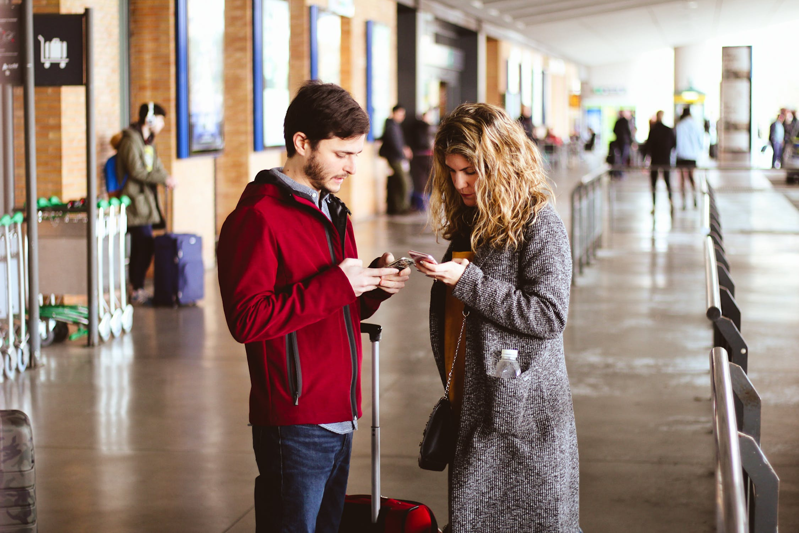 two people using cell phones in an airport