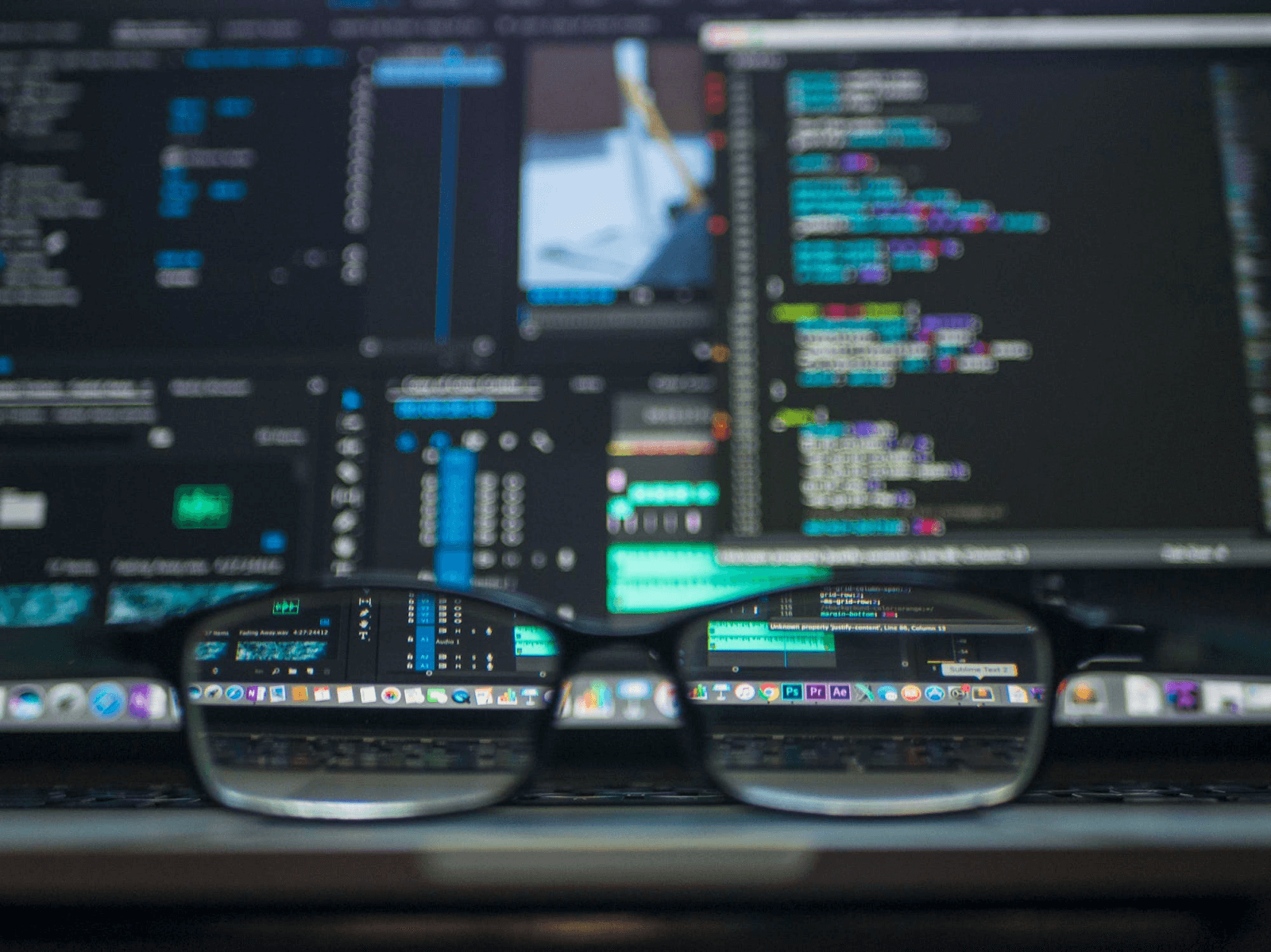 glasses in front of a blurred computer screen