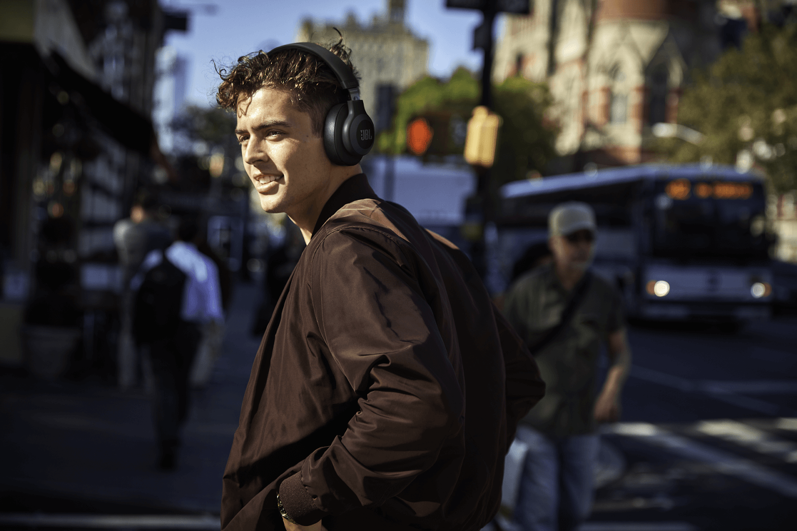 man walking down street wearing JBL wireless over the ear headphones