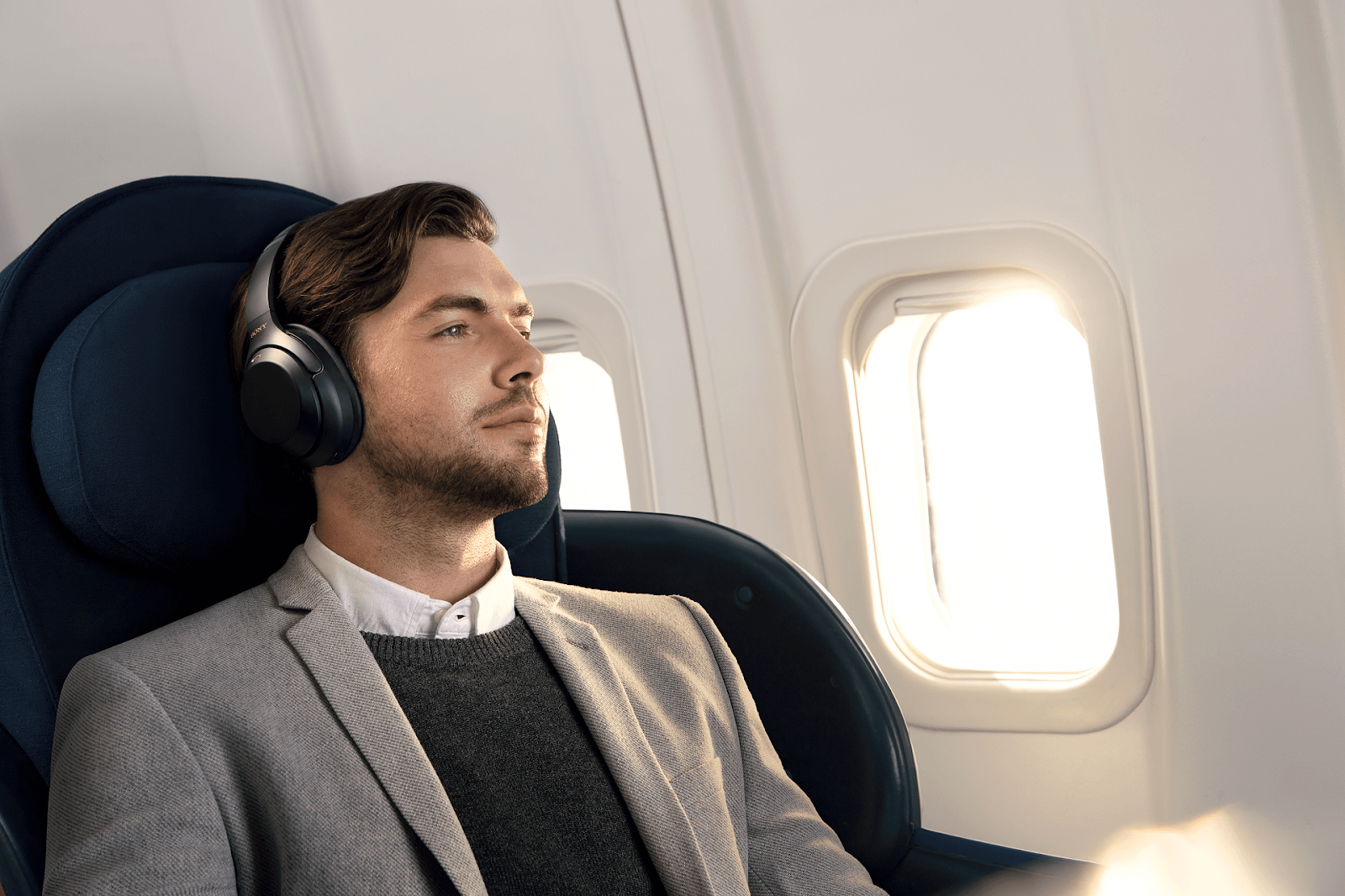 man in suit wearing headphones on a plane