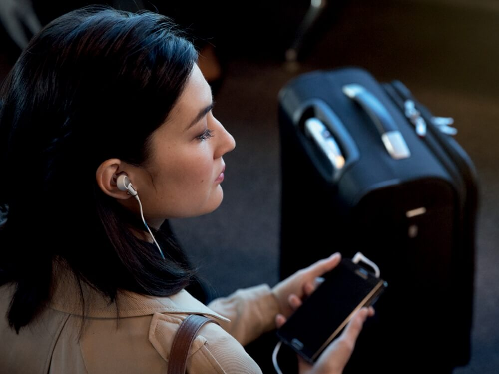 woman with suitcase and smartphone wearing bose quietcomfort 20 noise cancelling headphones