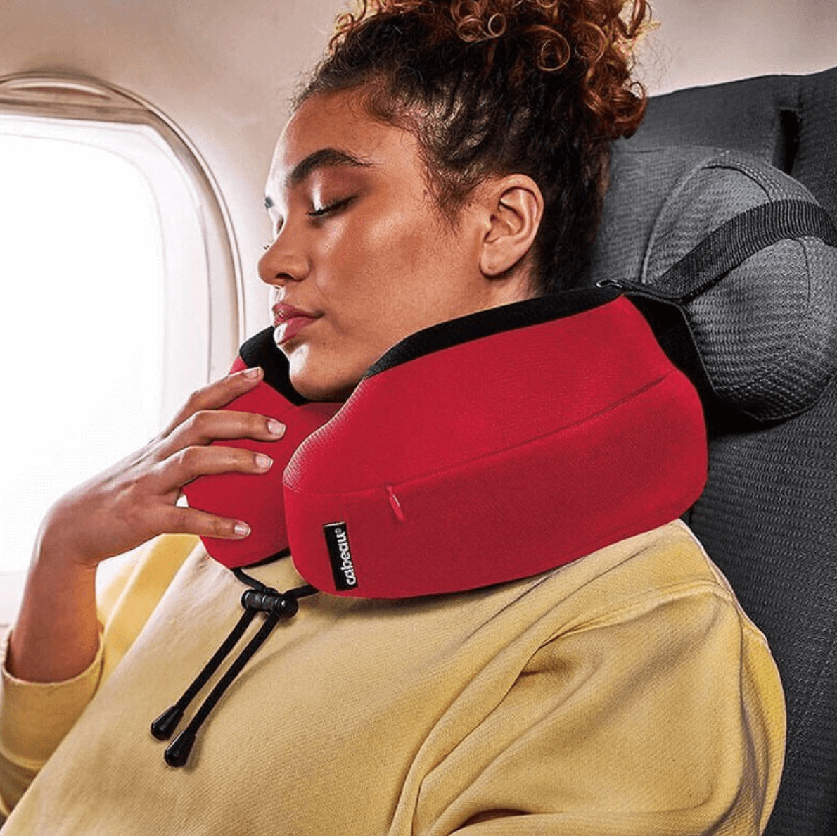woman on plane using cabeau neck pillow