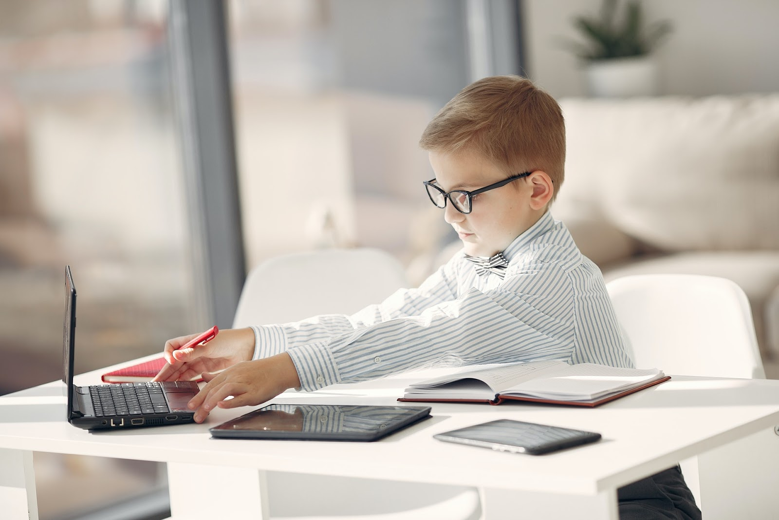 boy with glasses opening laptop