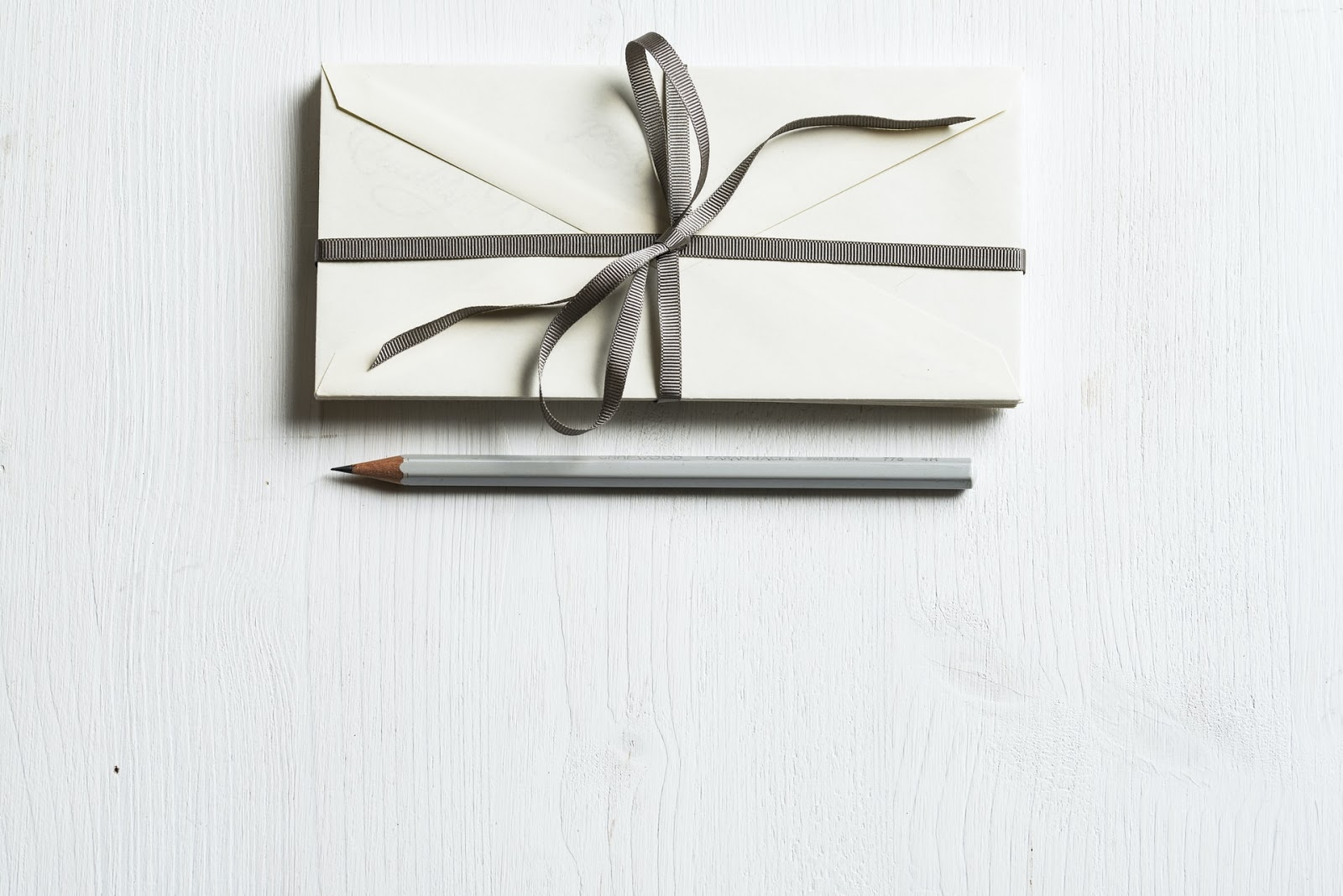 letter wrapped in ribbon and pencil