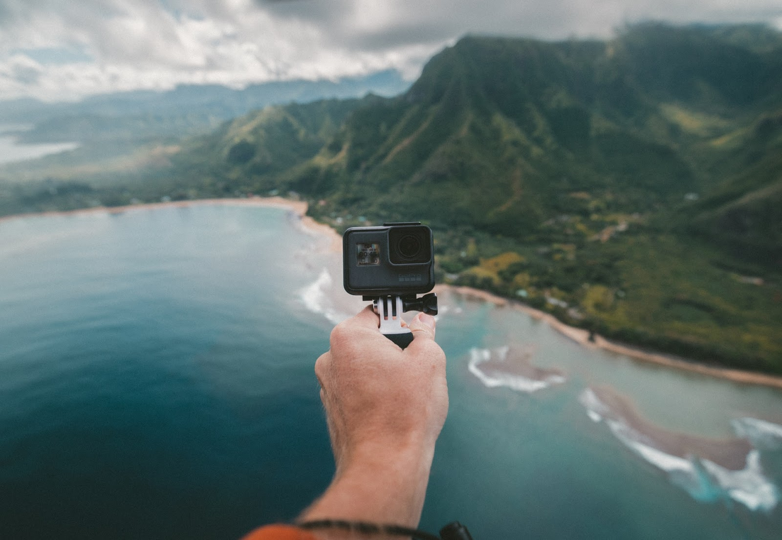 man holding gopro over cliff