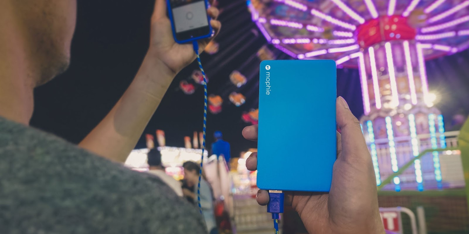 closeup of person using mophie powerstation mini at a carniva