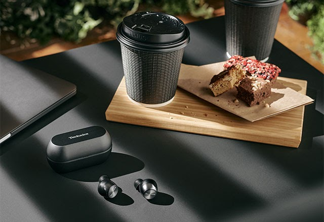 pair of black headphones placed near coffee cups and pastry